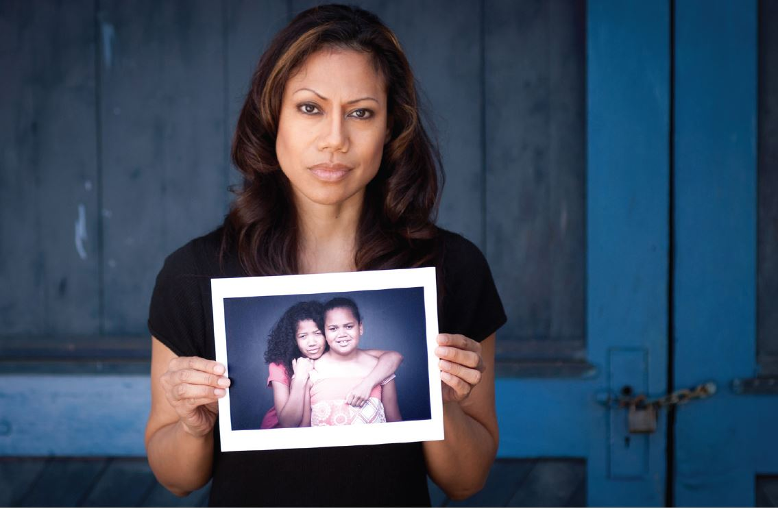 Woman holding photo of children
