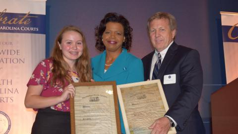 Walter Holton (right) and Mary Holton (left) present Chief Justice Cheri Beasley with Tabitha Holton's law license (photo credit: North Carolina Bar Association)